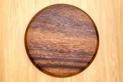 Top view of dark brown round wooden chopping block on light wood. Counter,Kitchenware Royalty Free Stock Image