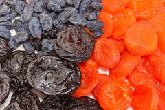 Some traditional dried fruits closeup at selective focus. Top view of dark-colored raisins, dried plums and dried apricots closeup at selective focus Royalty Free Stock Images