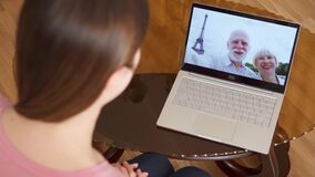 Woman at home having video chat via messenger app on laptop with senior parents from Paris, France. Top view of daughter at home having video chat via messenger stock footage
