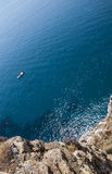 Top view of a deep blue sea and rocks of the coast. A little boa. T sailing in Sardinia Royalty Free Stock Images
