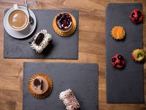Top view of delicious cakes of different flavours and colors over wooden table royalty free stock photos