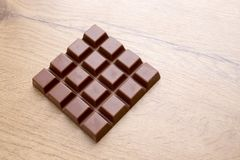 Delicious chocolate bar on wooden table. Top view of delicious chocolate bar on wooden table Stock Photography