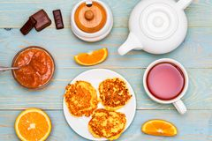 Cottage cheese cakes, tea, honey and quince jam. Top view delicious cottage cheese cakes or syrniki, honey, orange, sweets and quince jam on table for breakfast Royalty Free Stock Photos