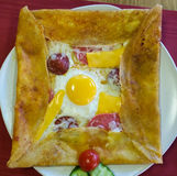 Top view of delicious crepe with bologna sausage, cheddar cheese, egg and salami served on a white plate Stock Photos