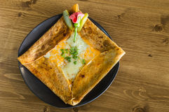 Top view of delicious crepe with cheddar cheese served on a grey plate Royalty Free Stock Images