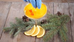 Top view on delicious dessert in glass bowl on wooden board decorated with fir-tree branches and slices of lemon. Isolated on black background. Chef hand puts stock video footage