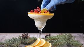 Top view on delicious dessert in glass bowl on wooden board decorated with fir-tree branches and slices of lemon. Isolated on black background. Chef hand puts stock footage