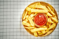 Top view of delicious french fries on plate with sauce on checkered tablecloth. Top view of delicious french fries on wooden plate with sauce on checkered stock images