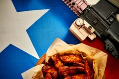 Top view of delicious fried chicken wings and machine gun with texas flag. Top view of delicious fried chicken wings and machine gun against texas flag stock image