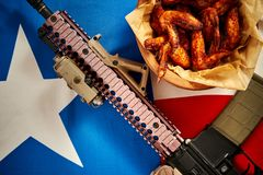 Top view of delicious fried chicken wings and machine gun with texas flag. Top view of delicious fried chicken wings and machine gun against texas flag stock photos