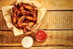Top view of delicious fried chicken wings with sauces on wooden table. Top view of delicious fried chicken wings with sauces on an old wooden table royalty free stock photos