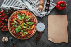 Top view of delicious pizza with cutter and blank paper. On concrete table Royalty Free Stock Photography