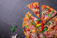 Top view of a delicious pizza with many meat, tomatoes and cheese on a gray stone background. Copy space. stock image