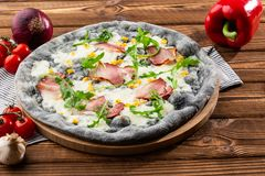 Top view of delicious Pizza on wooden table. Tasty pizza with ham, corn, rucola and cheese. Black pizza. stock images