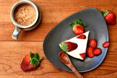 Top view of a slice of raw strawberry cake on a brown plate with wooden spoon. royalty free stock photos