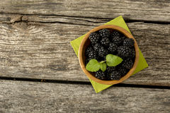 Top view of delicious ripe blackberries in a wooden bowl Royalty Free Stock Images