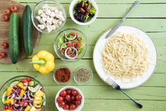 Top view of delicious spaghetti on plate and fresh raw vegetables. On wooden table Royalty Free Stock Image