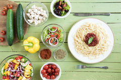 Top view of delicious spaghetti on plate and fresh raw vegetables. On wooden table Royalty Free Stock Photography