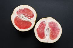 Closeup of juicy ripe grapefruit on dark surface.Constrast of colors in the nature. Top view of delicious tropical fruits on dark background.Fruits at night stock photos