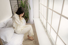 Top view of depressed asian woman sitting on bed stock photo