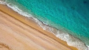 Top view of a deserted beach. Greek coast of the Ionian Sea. Aerial drone footage of sea waves reaching shore stock footage