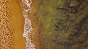 Top view of a deserted beach at sunset. Greek coast of the Ionian Sea. Aerial drone footage of sea waves reaching shore stock footage