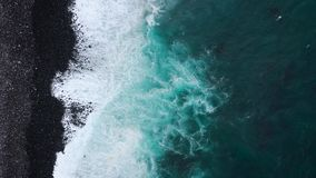 Top view of a deserted black volcanic beach. Coast of the island of Tenerife. Aerial drone footage of sea waves reaching stock video