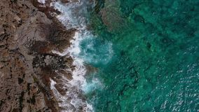 Top view of a deserted coast. Rocky shore of the island of Tenerife. Aerial drone footage of ocean waves reaching shore stock video footage