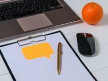 Top view of the designer`s workplace with laptop, tablet, pen and orange. Stock Photos