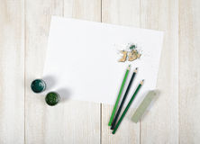 Top view of designer workplace equipped with green gouache jars, colored pencils, chalk, shavings and white paper Royalty Free Stock Photography