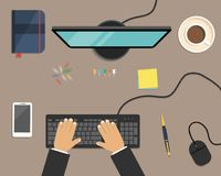 Top view of a desk background. There is a computer, smart phone, daily planner, stationery and cup of coffee. On a brown background. There are hands on the Stock Photo