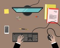 Top view of a desk background. There is a computer, smartphone, folders and other stationery on a brown background. There are also hands on the keyboard in the Stock Photo