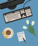 Top view of a desk background. There is a monitor, keyboard, a cup of coffee with cookies and white tulips on a blue background. Top view of a desk background Stock Photo