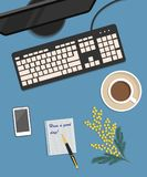 Top view of a desk background. There is a monitor, keyboard, cup of coffee and mimosa flowers on a blue background. Top view of a desk background. There is a Royalty Free Stock Photography