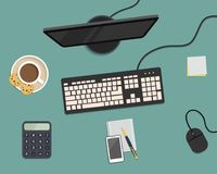 Top view of a desk background. There is a monitor, keyboard, mouse, smartphone, calculator and other stationery on a blue backgrou. Nd. Also there is a cup of Stock Image