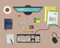 Top view of a desk background, where there is a monitor, keyboard, computer mouse, color folders, markers, other stationery Royalty Free Stock Photos