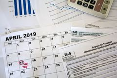 Top view of desk with calculator, tax forms, graphs and calendar sheet with tax date marked royalty free stock image