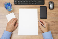 Top view of desk with empty paper and man with pen in hand, read Royalty Free Stock Photos