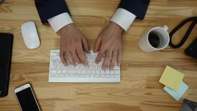 Top view of desk with office supplies. Man typing on his laptop and drinking coffee Stock Image