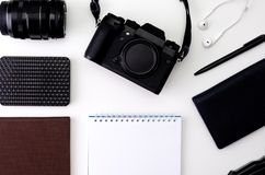 Top view desk workspace with laptop keyboard, hipster camera, lens, headphones, notepad for writing with black pen on royalty free stock photography