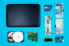 Top view of desktop of  hardware engineer. On blue background. Black laptop with connectors, microcontroller, hdd and hardware equipment Stock Image