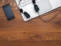 Top view on the desktop. With laptop, phone and headphones Royalty Free Stock Photos