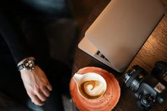 Top view of the desktop on which there is a cup of coffee, a laptop and a modern professional camera. Man photographer works at a table in a cafe. Modern royalty free stock photo