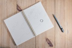 Top view of Diamond ring on white notebook have letter ` WILL YOU MARRY ME` and gray pencil on wooden table Stock Photo