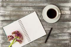 Top view of a diary or notebook, pencil and coffee and a purple flower on a gray wooden table. Flat design. Top view of a diary or notebook, pencil and coffee royalty free stock photography