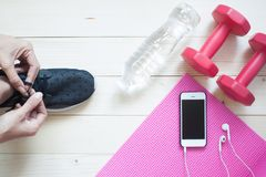 Top view of Diet and Fitness concept, woman tying shoes with sma. Rt phone on yoga mat Royalty Free Stock Images
