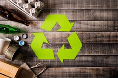 Top view of Different garbage materials with recycling symbol on table background. Recycle, World Environment Day and Eco concept.  royalty free stock images