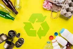 Top view of Different garbage materials with recycling symbol on table background. Recycle, World Environment Day and Eco concept.  royalty free stock photo