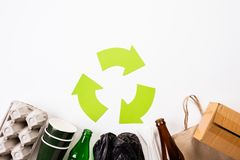 Top view of Different garbage materials with recycling symbol on white wooden table background. Recycle, World Environment Day and. Eco concept stock image