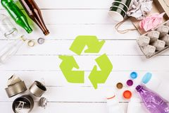 Top view of Different garbage materials with recycling symbol on white wooden table background. Recycle, World Environment Day and. Eco concept royalty free stock image